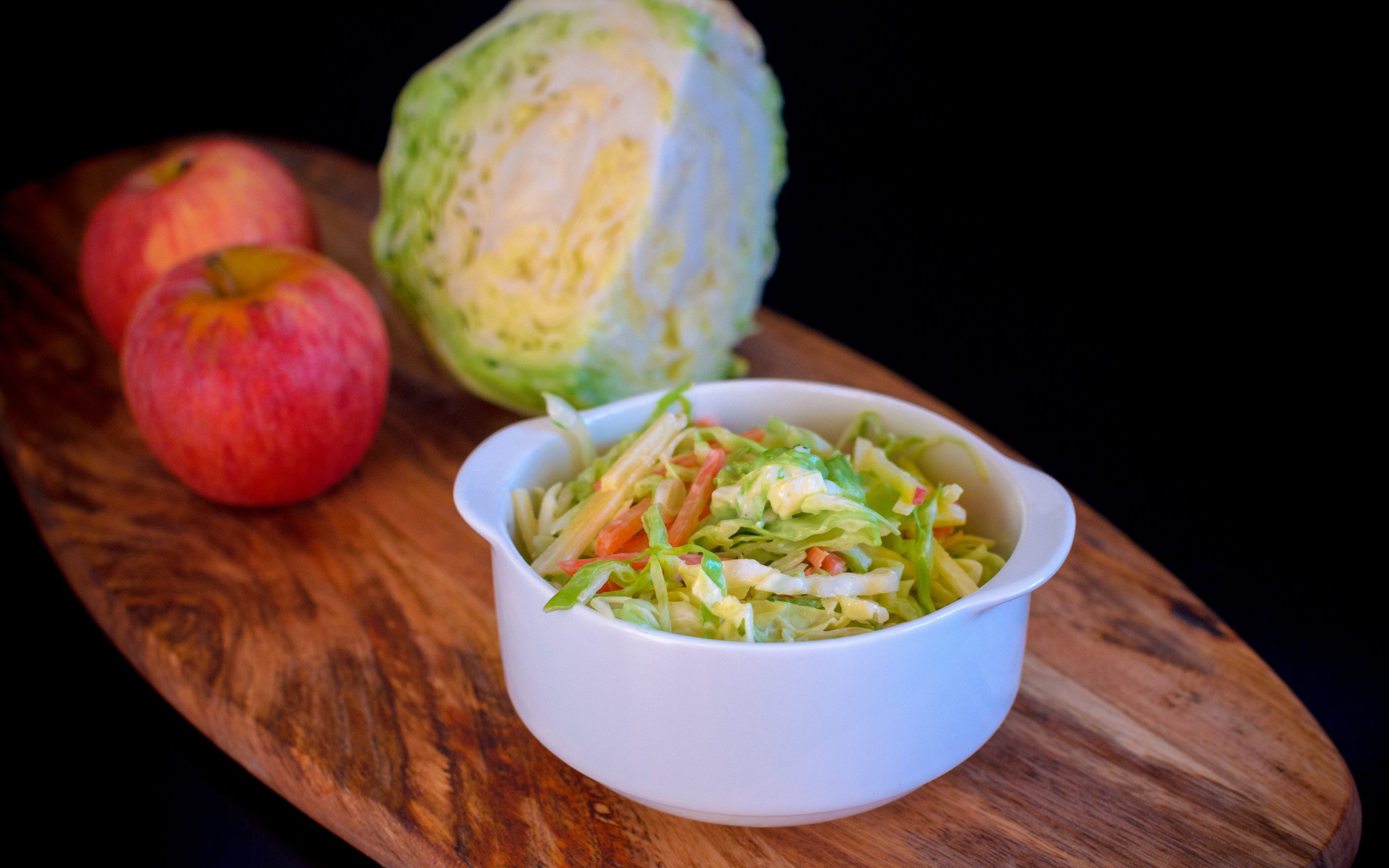 Homemade coleslaw salad in a white plate with cabbage and apple on a wooden board on a black background.